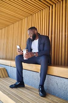 Imagen de un hombre con un teléfono y una botella de agua en las manos
