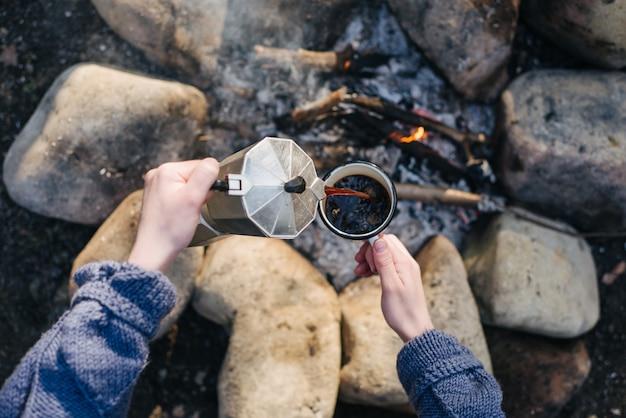 Imagen horizontal al aire libre de la mujer joven se vierte bebida caliente cerca de la hoguera.