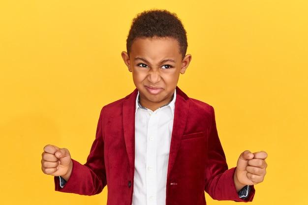 Imagen horizontal del colegial afroamericano enojado emocional manteniendo los puños cerrados, enojado por el fracaso.