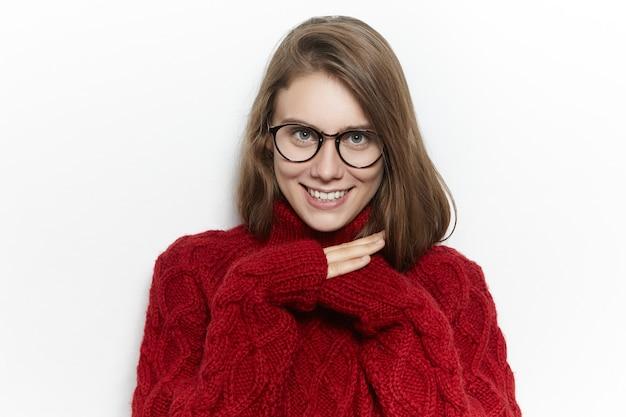 Imagen horizontal de una linda adolescente alegre con un suéter de cuello alto granate mientras pasa el frío día de otoño en casa, calentando, escondiendo las manos dentro de las mangas y sonriendo felizmente