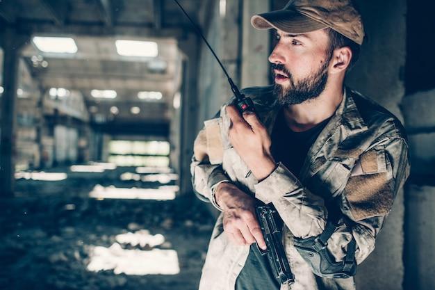 Imagen horizontal de soldado hablando con radio portátil. lo está sosteniendo en la mano izquierda. hay una pistola en la mano derecha. también luchador está mirando hacia adelante.