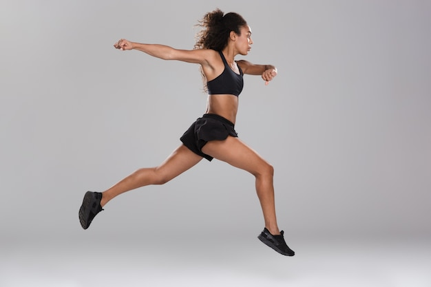 Imagen de increíble hermosa mujer fuerte deportes saltando aislado.