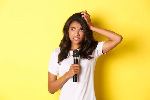 Imagen de indecisa niña afroamericana sosteniendo el micrófono y mirando de pie vacilante