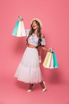 Imagen integral de alegre joven vistiendo sombrero de paja y falda esponjosa sonriendo y sosteniendo coloridos paquetes de compras de papel