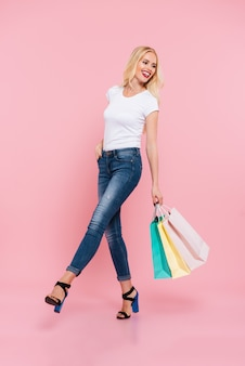 Imagen integral de feliz mujer rubia despreocupada caminando con paquetes y mirando hacia atrás sobre rosa