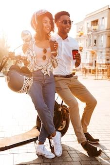 Imagen integral de la feliz pareja africana joven tomando café mientras está de pie cerca de la moto moderna en la calle y mirando a otro lado