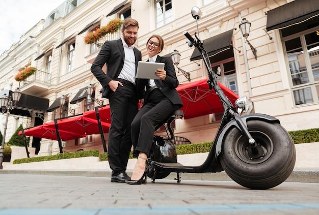 Imagen integral de la feliz pareja de negocios posando cerca de moto