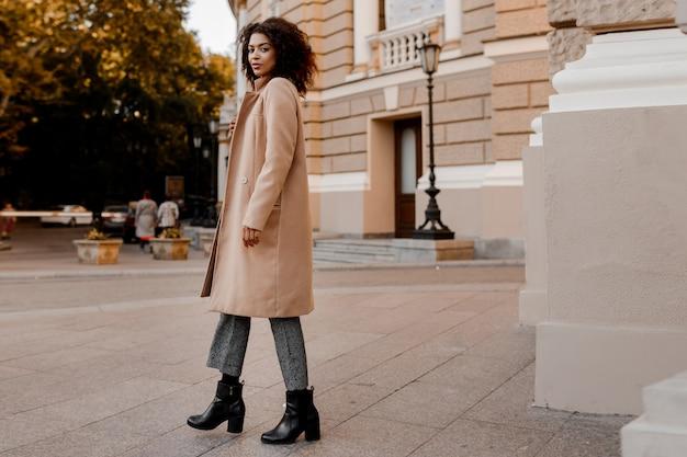 Imagen integral de moda de mujer negra elegante con elegante abrigo beige de lujo y suéter de terciopelo