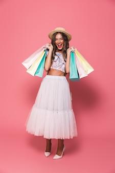 Imagen integral de mujer adicta a las compras con sombrero de paja y falda esponjosa sonriendo y sosteniendo bolsas de papel de colores