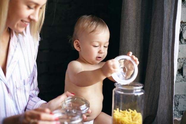 Imagen interior de adorable niño feliz en pañal jugando con la tapa de la botella de vidrio en la cocina, su hermosa joven madre sentada junto a él, sonriendo ampliamente. enfoque selectivo en la cara del bebé.