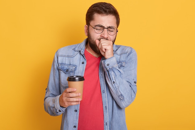 Imagen interior de un cansado y cansado chico barbudo que se lleva las manos a la boca, bosteza, tiene ganas de dormir, sostiene el café en una taza de papel