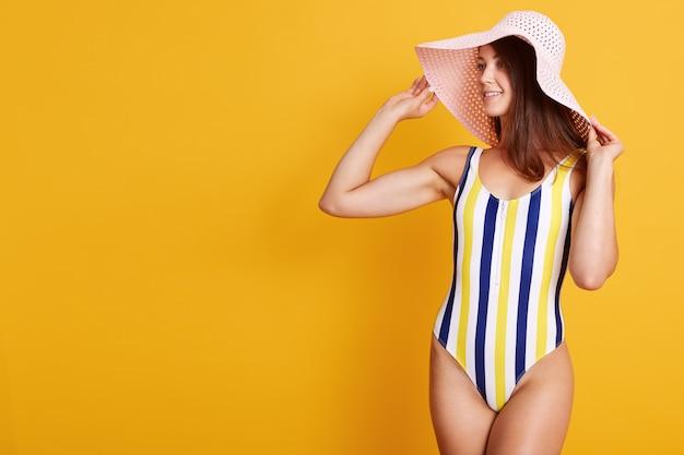 Imagen interior de mujer joven con cabello oscuro con elegante traje de baño a rayas, mirando a un lado aislado en amarillo, mantiene una mano en su sombrero, copia espacio para publicidad o texto de promoción.