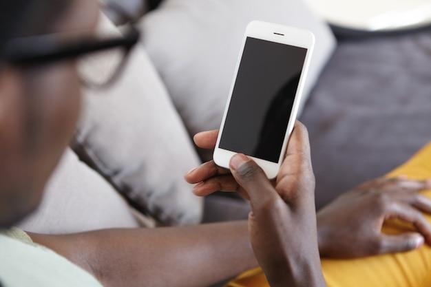 Imagen interior recortada de un hombre de piel oscura irreconocible descansando en el sofá de la sala de estar, usando el wifi de su casa en un teléfono móvil moderno
