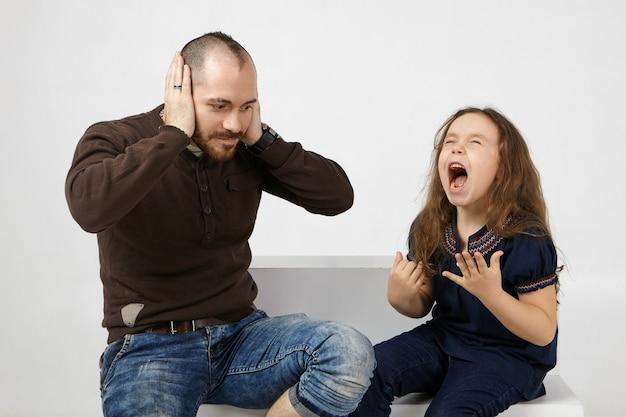 Imagen de un joven sin afeitar sorprendido con ropa elegante que cubre las orejas debido a una niña malcriada y traviesa que llora y grita en voz alta.