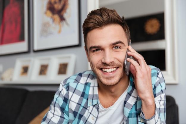 Imagen de un joven alegre vestido con camisa en una jaula de impresión sentado en el sofá en casa y hablando por su teléfono.