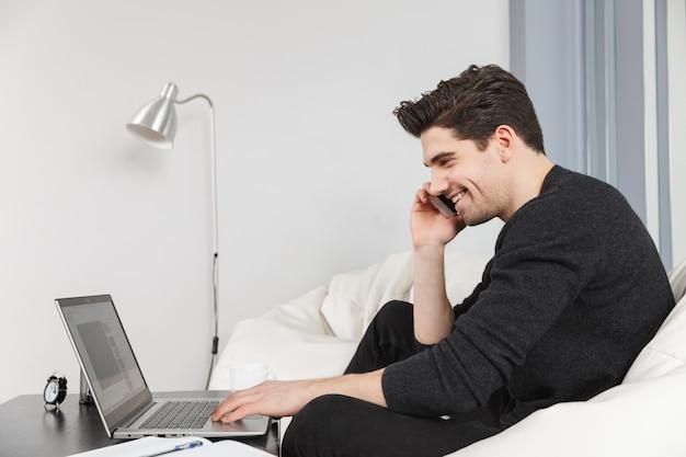 Imagen de un joven apuesto feliz en casa en el interior con ordenador portátil hablando por teléfono móvil.