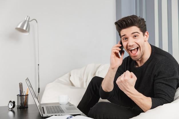 Imagen de un joven apuesto feliz en casa en el interior con ordenador portátil hacer gesto de ganador hablando por teléfono móvil.