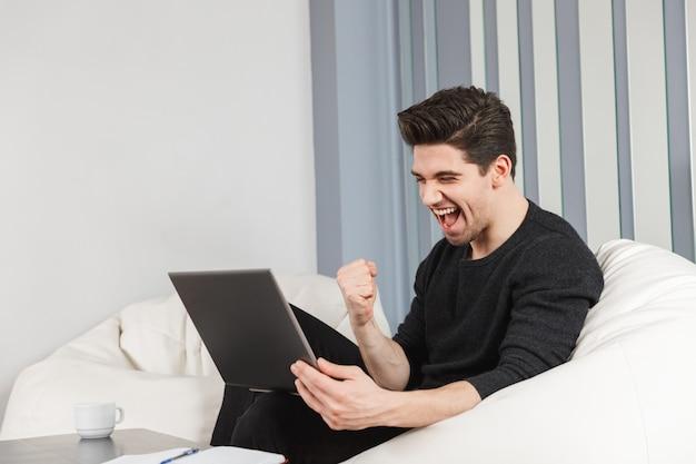 Imagen de un joven apuesto feliz en casa en el interior con ordenador portátil hacer gesto de ganador.