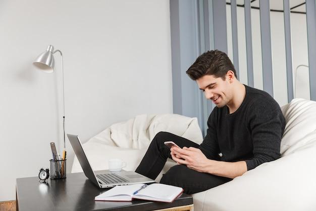 Imagen de un joven apuesto feliz en casa en el interior con ordenador portátil mediante teléfono móvil.
