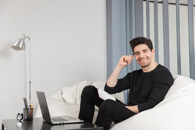 Imagen de un joven apuesto feliz en casa en el interior con ordenador portátil.