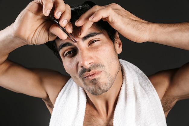 Imagen de un joven apuesto que presenta forma de cejas correctas aisladas con pinzas.