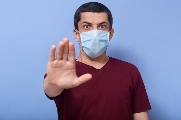 Imagen de un joven asustado y sorprendido con expresión facial asustada, abriendo mucho los ojos, levantando una mano, usando una máscara antibacteriana, manteniendo distancia de las personas. concepto de propagación de coronavirus.
