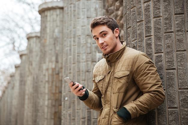 Imagen de joven atractivo caminando por la calle y charlando por su teléfono al aire libre. mira la cámara.