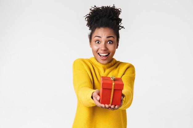 Imagen de una joven y bella mujer africana feliz posando sobre una pared blanca sosteniendo el cuadro actual.