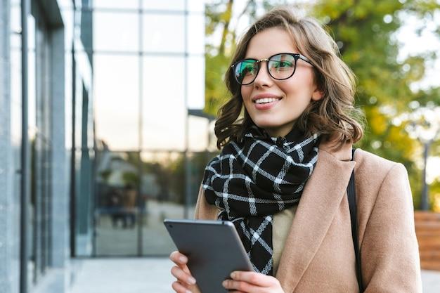 Imagen de una joven y bella mujer al aire libre caminando por la calle con tablet pc.