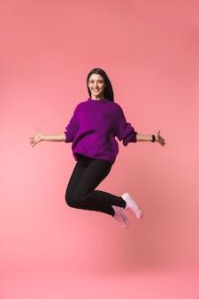 Imagen de una joven y bella mujer emocional posando aislada sobre rosa saltando del espacio.