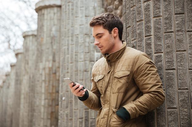 Imagen de un joven caminando por la calle y charlando con su teléfono al aire libre. mira el teléfono.
