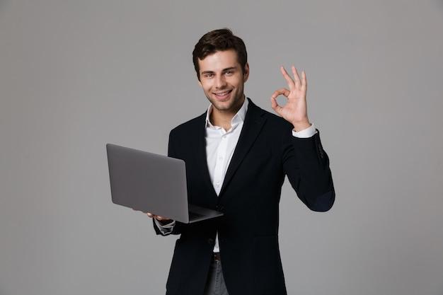 Imagen del joven empresario de 30 años en traje de regocijo mientras usa la computadora portátil, aislado sobre pared gris