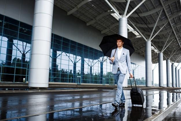 Imagen del joven empresario pelirrojo con paraguas negro y maleta caminando bajo la lluvia en la estación