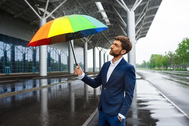 Imagen del joven empresario sosteniendo coloridos paraguas con chispitas alrededor en la calle lluviosa