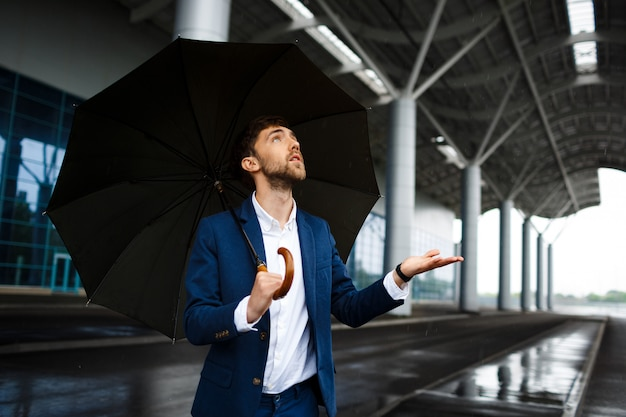 Imagen del joven empresario sosteniendo paraguas bajo la lluvia mirando las gotas