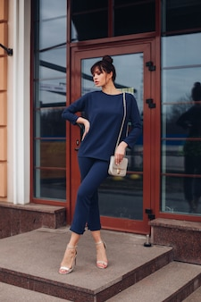 Imagen de joven encantadora mujer caucásica con cabello oscuro en blusa azul oscuro y pantalón azul oscuro, zapatos blancos con bolsa blanca