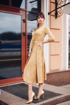 Imagen de joven encantadora mujer caucásica con cabello oscuro en vestido dorado y zapatos dorados muestra diferentes stands cerca del hermoso edificio