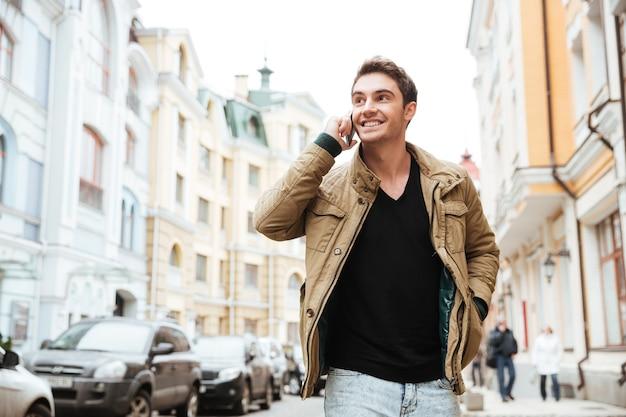 Imagen de un joven feliz caminando por la calle y mirando a un lado mientras habla por su teléfono.