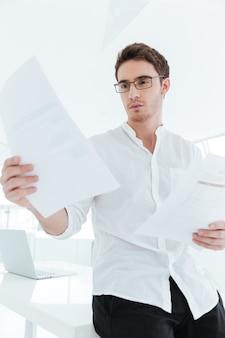 Imagen de joven feliz vestido con camisa blanca con documentos. mirando papel.
