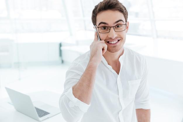 Imagen de joven feliz vestido con camisa blanca hablando por teléfono. mirando a la cámara.