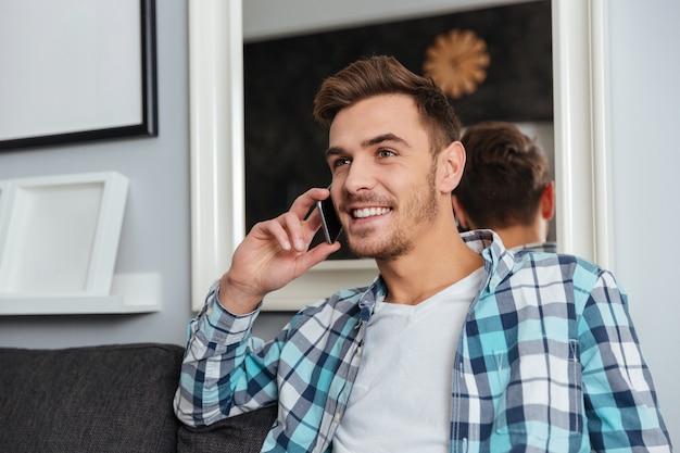 Imagen de un joven feliz vestido con camisa en una jaula de impresión sentado en el sofá en casa y hablando por su teléfono.
