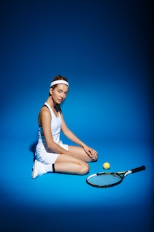 Imagen de la joven fintess cerca de la raqueta de tenis y sentada en el piso