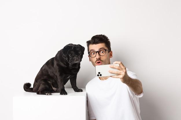 Imagen de joven guapo tomando selfie con lindo perro negro en smartphone, posando con pug sobre fondo blanco.