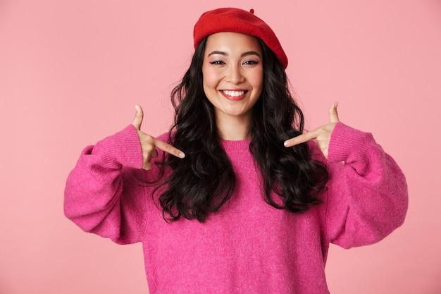 Imagen de joven hermosa chica asiática con boina riendo y señalando con el dedo a sí misma