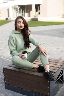 Imagen de joven mujer caucásica con pelo largo y oscuro en sudadera con capucha, pantalones deportivos y zapatillas negras bebe café en el verano