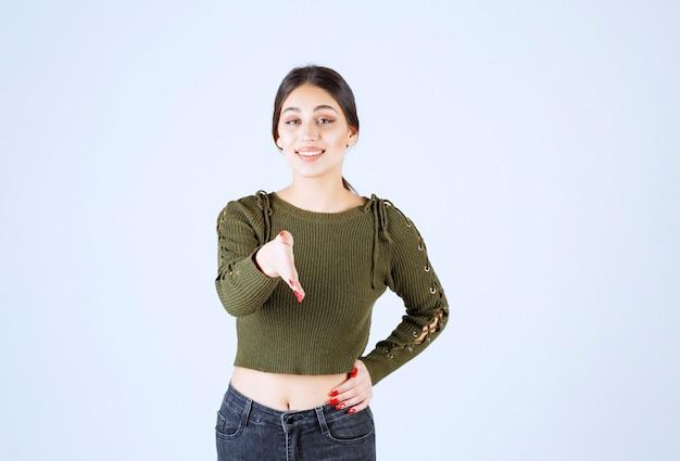 Imagen de una joven mujer sonriente ofreciendo la palma de la mano dando asistencia y aceptación.