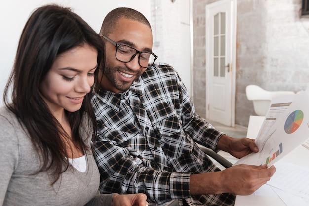 Imagen de la joven pareja de negocios feliz en la oficina trabajando con documentos. mira el diagrama.