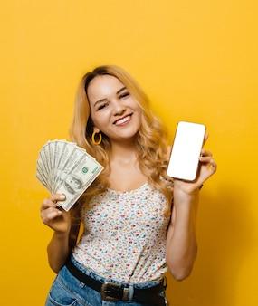 Imagen de una joven rubia emocional con billetes y un teléfono celular de pantalla negra en una pared amarilla