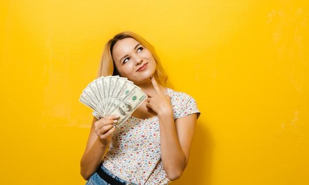 Imagen de una joven rubia feliz celebración de billetes sobre yellowwall
