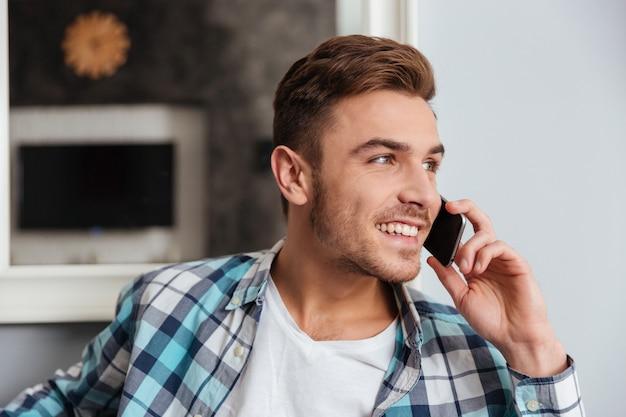 Imagen de un joven sonriente vestido con camisa en una jaula de impresión sentado en el sofá en casa y hablando por su teléfono. mirando a un lado.
